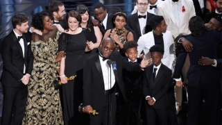 "'Moonlight' director Barry Jenkins, center, along with cast and producers celebrate their ""Best Picture"" win at the Academy Awards on February 26, 2017 (Chris Pizzello/Invision/AP)"